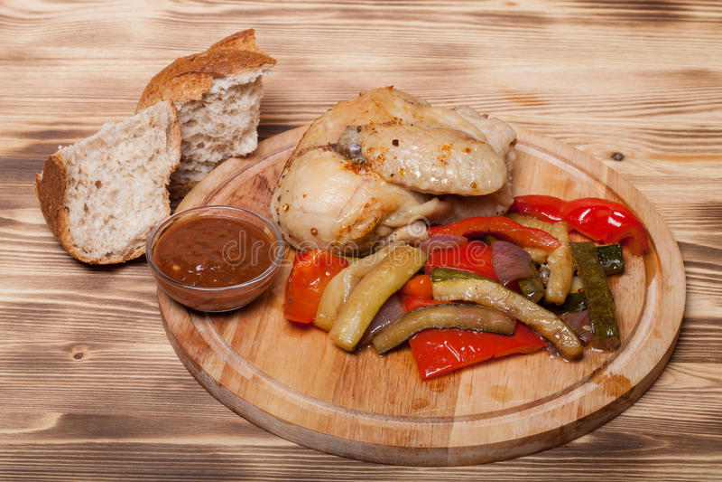 Le poulet avec des légumes a servi sur la planche à découper ronde sur brûlé images libres de droits