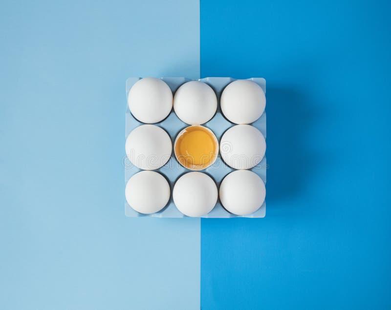 Le poulet cru blanc eggs sur le fond bleu coloré photographie stock