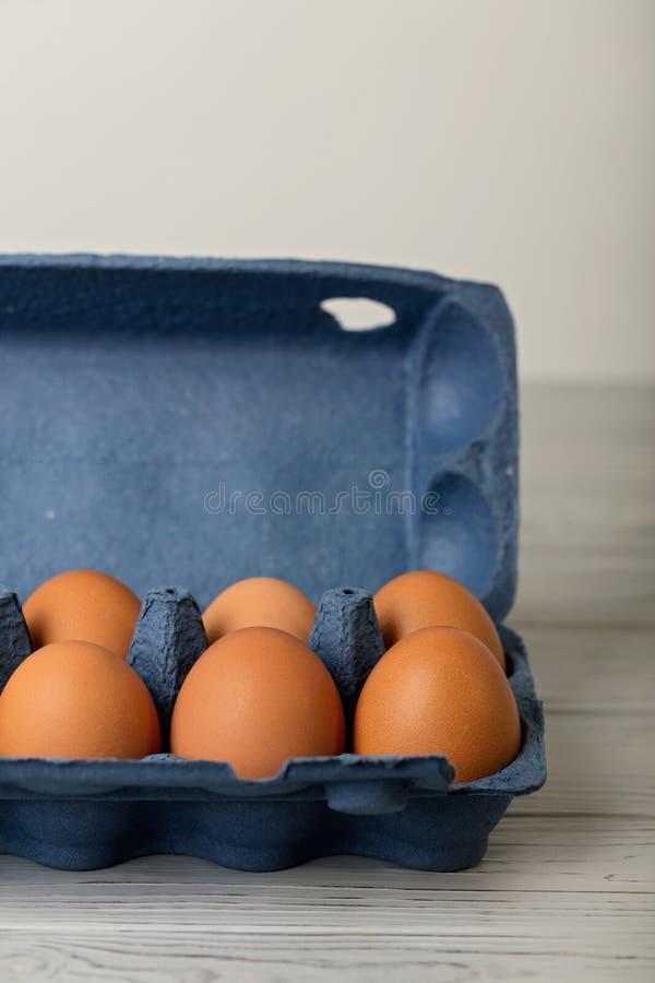 Le poulet eggs dans un paquet bleu sur un fond en bois gris images libres de droits