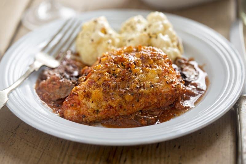 Le poulet en vin rouge avec la miette et la châtaigne de lard répand images libres de droits