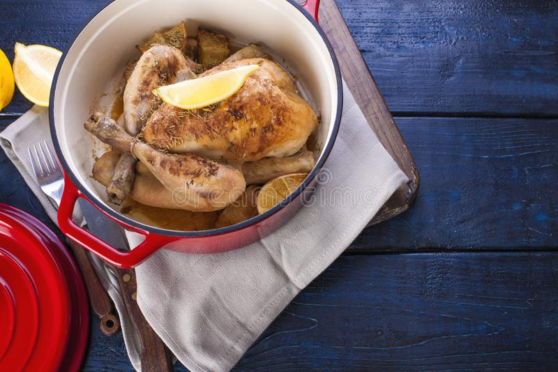 Le poulet entier a fait cuire au four avec le citron et le romarin dans une fonte rouge Fond en bois bleu et serviette grise Cout images libres de droits