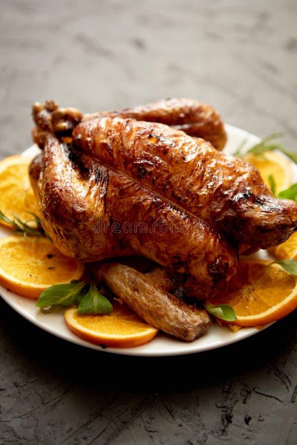 Le poulet entier ou la dinde rôti a servi dans le plat en céramique blanc avec des oranges photo stock