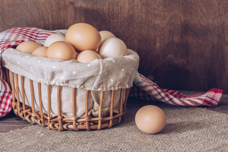 Le poulet frais eggs dans un panier sur une table en bois Serviette de toile sur la table images stock
