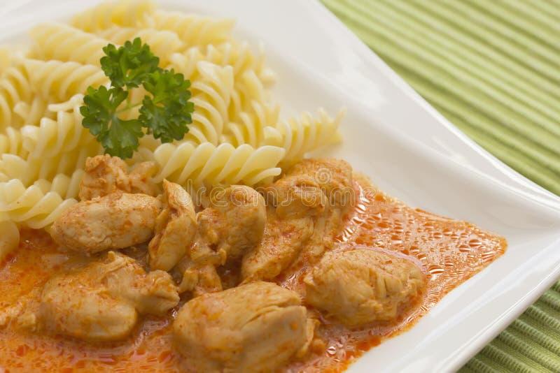 Le poulet rapièce avec des pâtes en sauce crème à paprika. images libres de droits