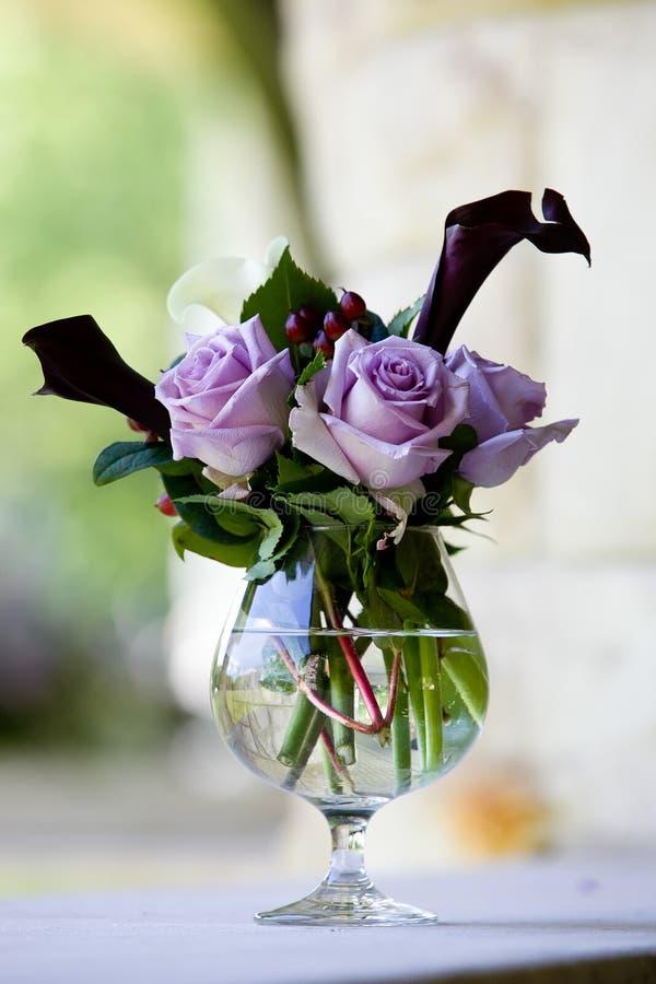 Le pourpre a monté bouquet sur une table pendant une célébration l'épousant photo libre de droits
