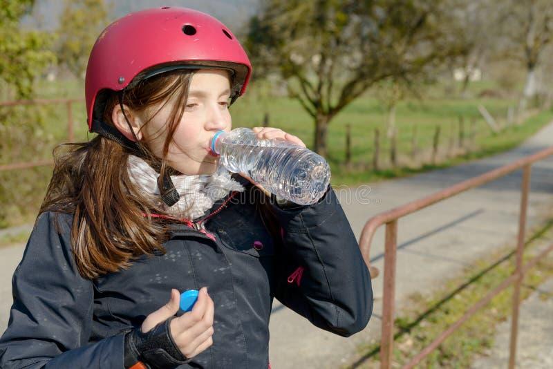 Le préadolescent avec le casque de patin de rouleau, boivent une eau photos libres de droits