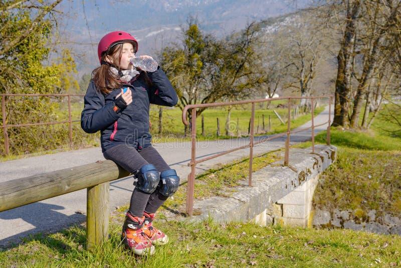 Le préadolescent avec le casque de patin de rouleau, boivent une eau images libres de droits