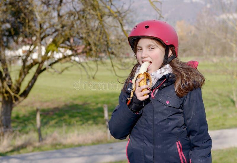 Le préadolescent avec le casque de patin de rouleau, mangent la banane photographie stock libre de droits