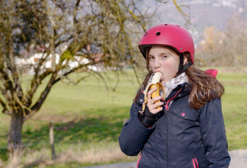 Le préadolescent avec le casque de patin de rouleau, mangent la banane image stock