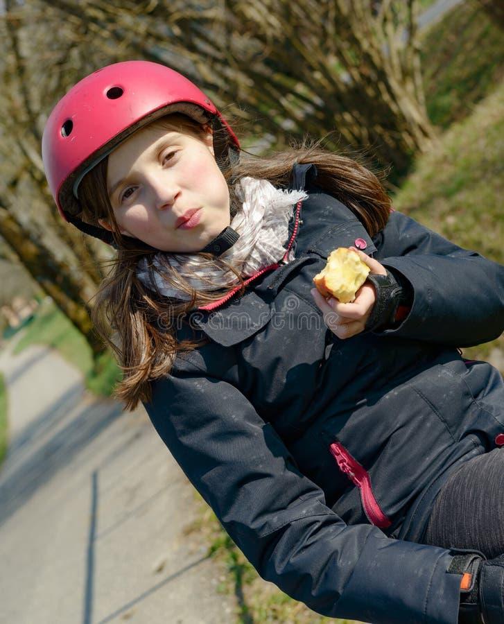 Le préadolescent avec le casque de patin de rouleau, mangent une pomme photos libres de droits
