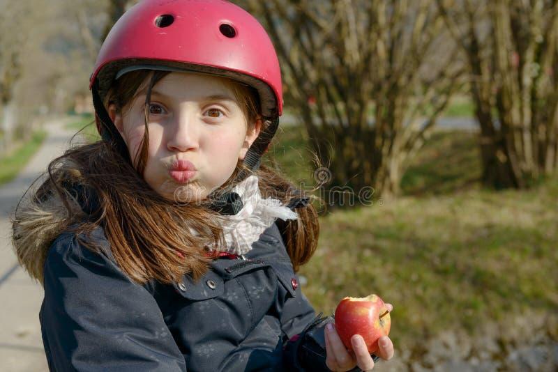 Le préadolescent avec le casque de patin de rouleau, mangent une pomme photographie stock