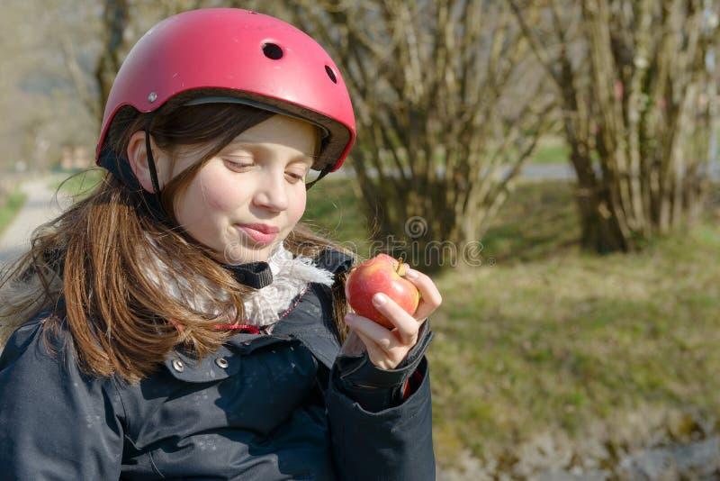 Le préadolescent avec le casque de patin de rouleau, mangent une pomme image libre de droits