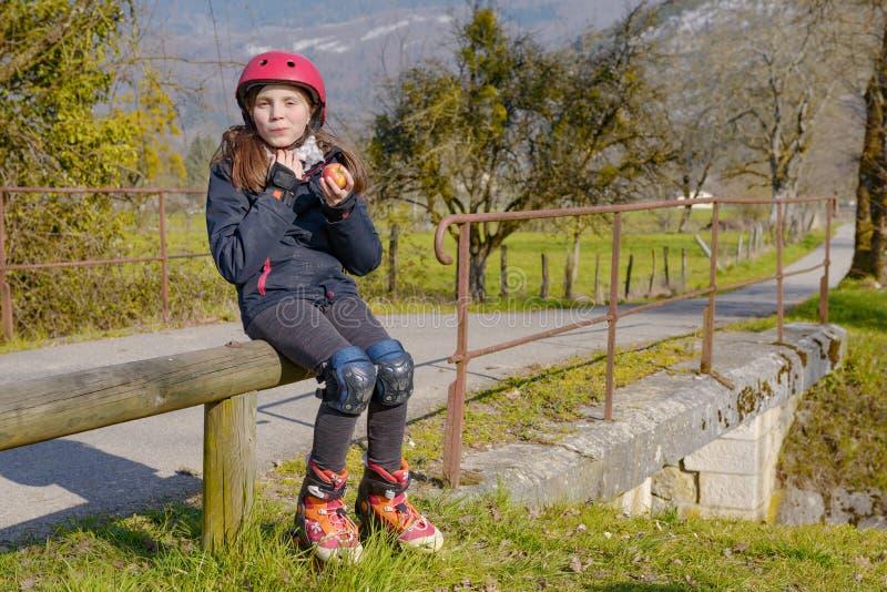 Le préadolescent avec le casque de patin de rouleau, mangent une pomme photos stock