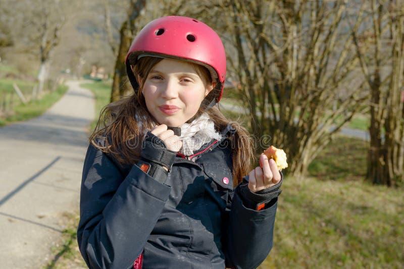 Le préadolescent avec le casque de patin de rouleau, mangent une pomme images libres de droits