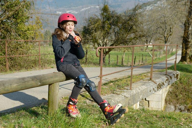 Le préadolescent dans le patin de rouleau, mangent une pomme image stock