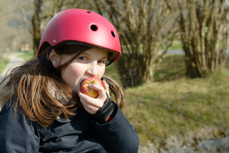 Le préadolescent dans le patin de rouleau, mangent une pomme photos stock
