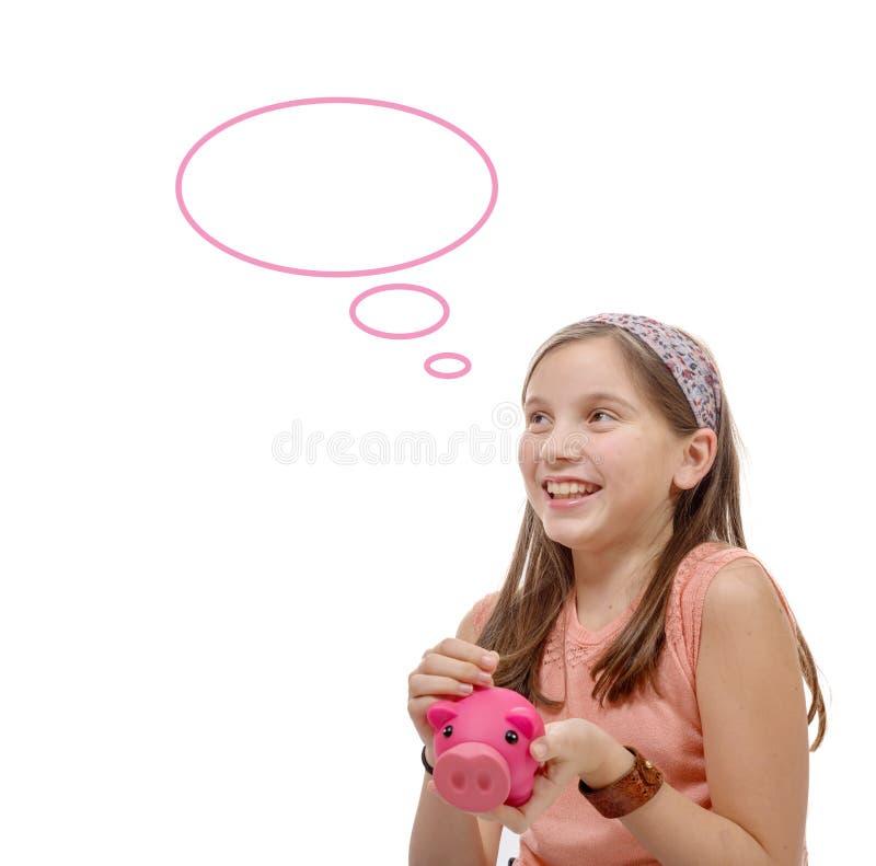 Le préadolescent pensent avec une tirelire, sur le blanc image libre de droits