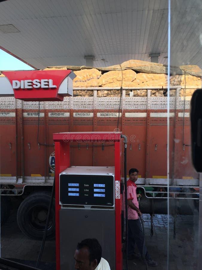Le préposé de pompe à essence remplit réservoir de camion au saberkanthat Goudjerate INDE image libre de droits