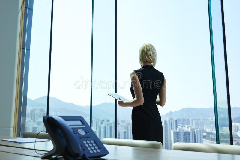 Le Président fier de femme avec le comprimé numérique dans des mains réfléchies regarde dans la fenêtre de bureau photographie stock