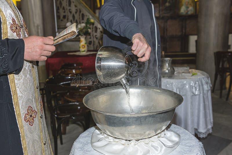 Le prêtre bénit la police baptismale de baptême remplie avec de l'eau saint à l'église pendant la cérémonie photos stock