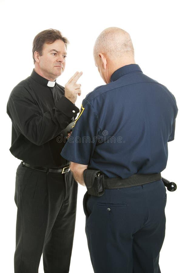 Le prêtre bénit le policier images libres de droits