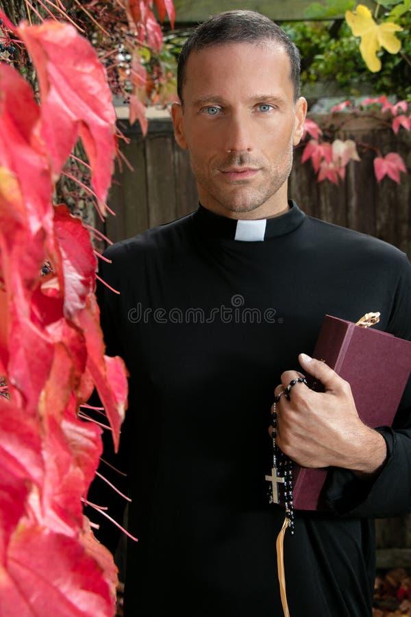 Le prêtre beau se tient dans le jardin tenant sa bible à côté du lierre de plante grimpante de Virginie photo stock