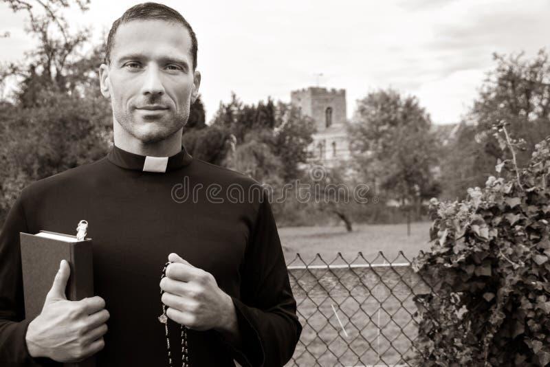 Le prêtre beau se tient devant la barrière pour mettre en place avec l'église à l'arrière-plan photo stock