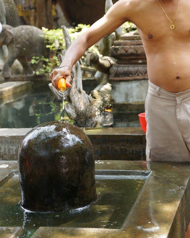 Le prêtre de Brahmin offre le puja au lingam de shiva image libre de droits