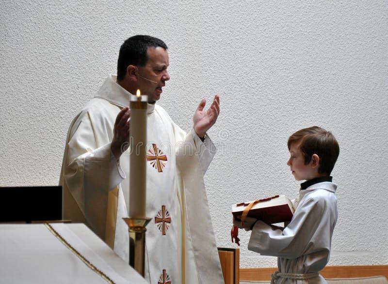 Le prêtre et modifient le garçon images libres de droits