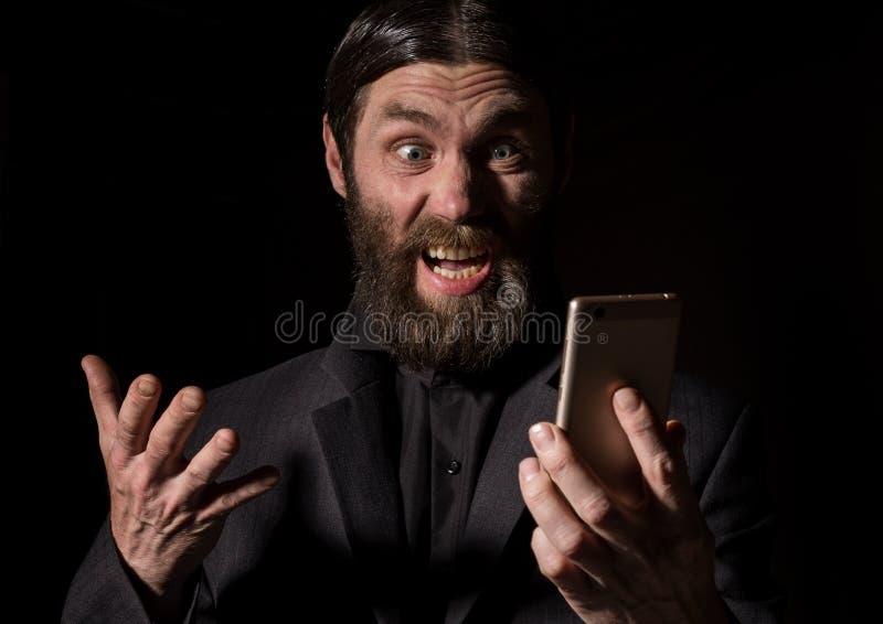 Le prêtre supérieur de vieux croyant avec un smartphone, vieil homme barbu invite un fond foncé photo libre de droits