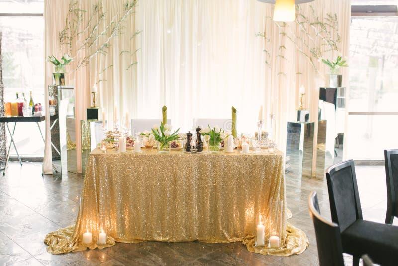 Le praesidium des nouveaux mariés au mariage, une table pour les jeunes mariés avec une nappe avec des paillettes d'or photos libres de droits