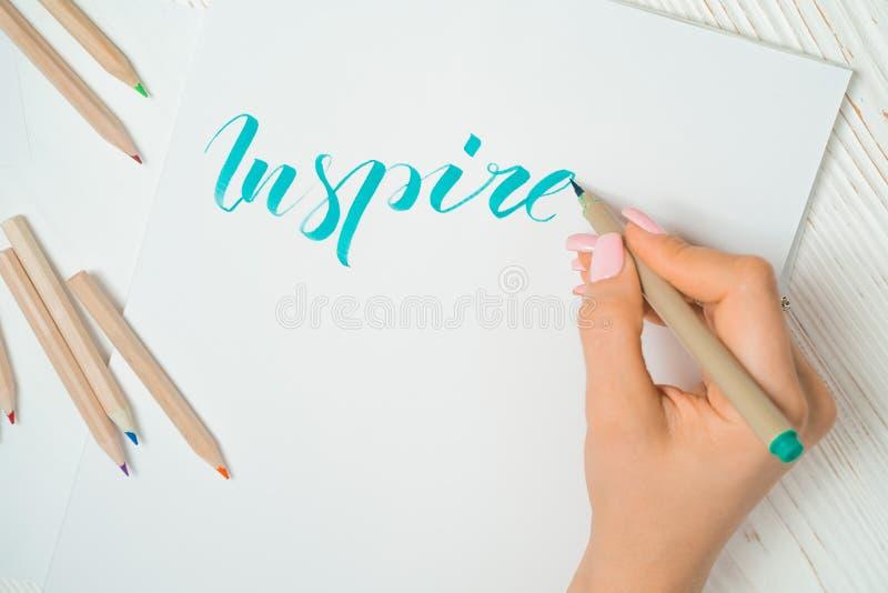 Le pratiche dello studente del calligrafo nella parola di scrittura ispirano con l'indicatore verde su tela Funzionamento creativ immagini stock