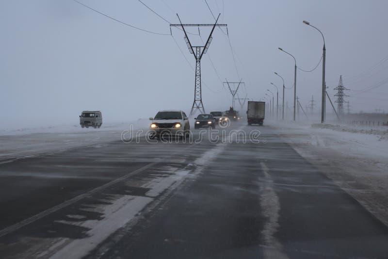 Le precipitazioni nevose che peggiorano il vento della bufera di neve del tempo spazzano la neve sulla strada in cui le automobil immagini stock libere da diritti