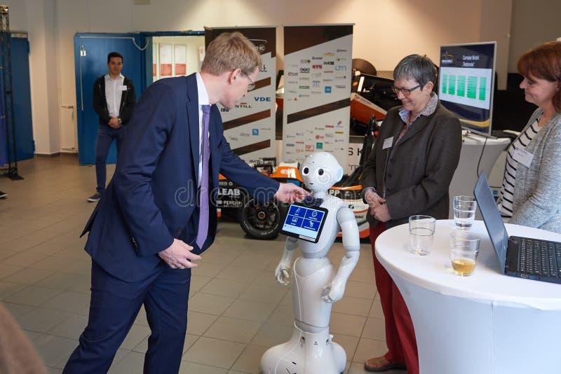 Le premier ministre nther de ¼ de Daniel GÃ agit l'un sur l'autre avec un robot de soin infirmier photographie stock libre de droits