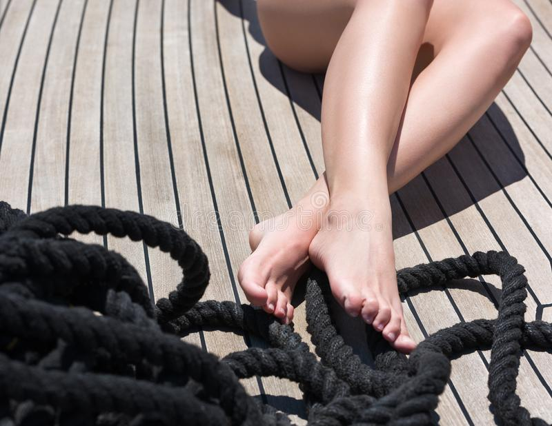 Le prenez un bain de soleil sur la plate-forme du bateau Fermez-vous des pieds femelles sur le plancher en bois photo libre de droits