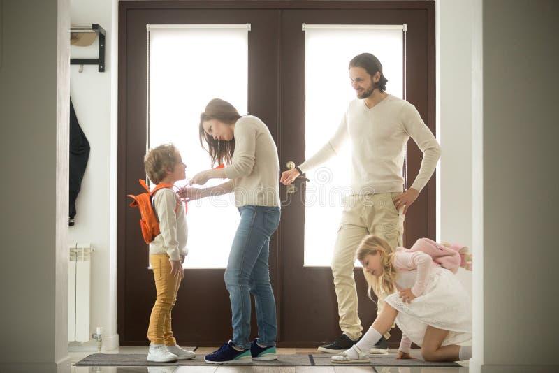 Le preparazioni felici di mattina della famiglia, genitori che ottengono i bambini aspettano le FO fotografia stock