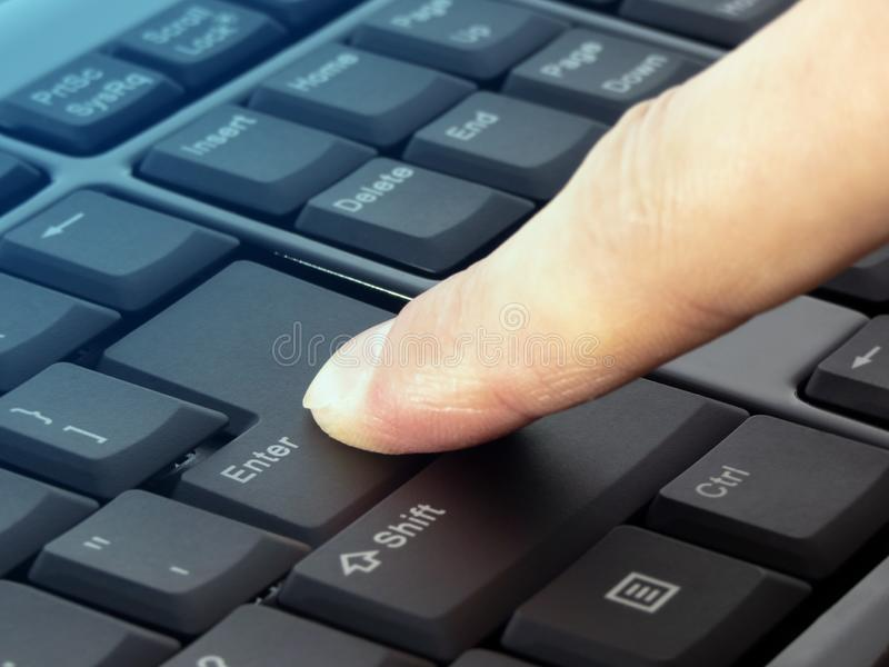 Le pressurage de doigt entrent dans le bouton sur le clavier noir photos stock