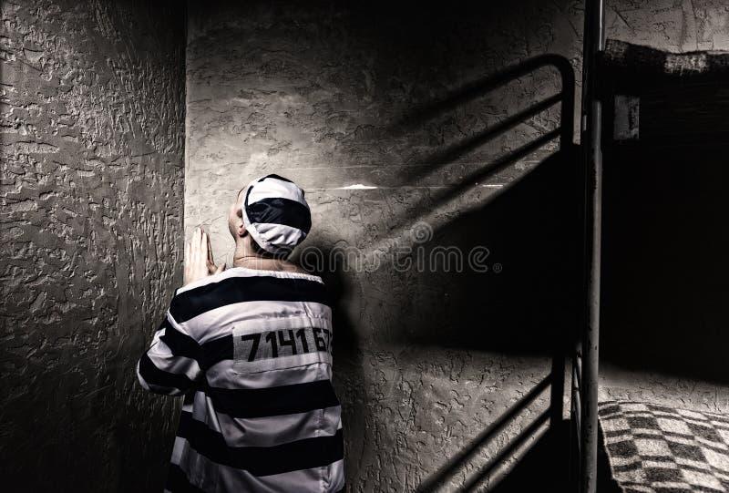 Le prisonnier masculin s'assied dans le coin et prie dans de petites RP image stock