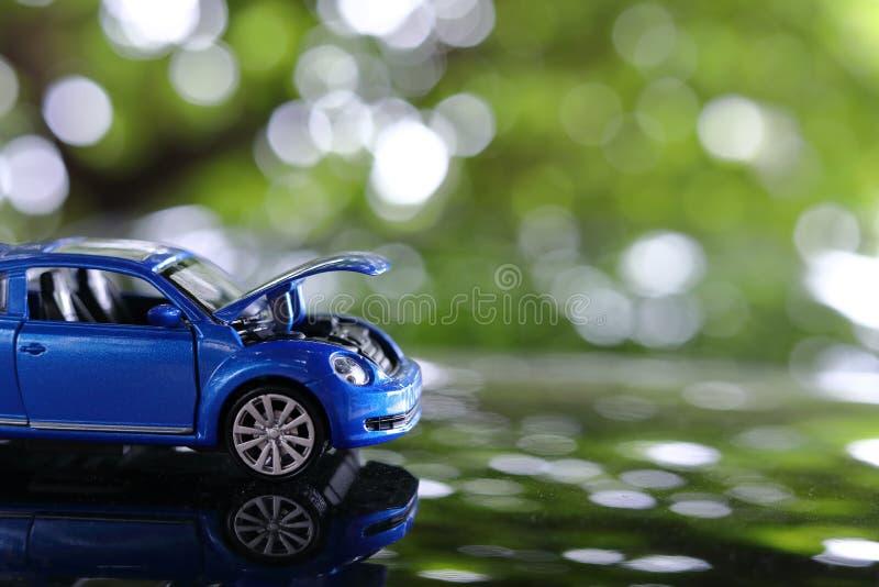 Le problème de jouet de voiture décomposé s'est garé avec le capot ouvert du véhicule photo stock