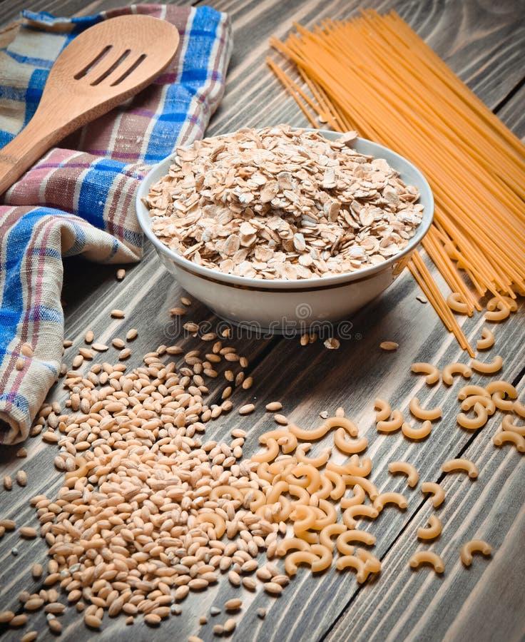 Le procédé de cuisson Une cuvette de farine d'avoine crue, de céréales, de pâtes, de cuillère en bois et d'une serviette sur une  photo libre de droits