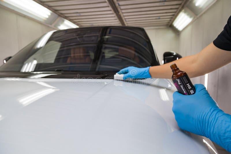 Le processus d'application d'un revêtement nano-céramique Ceramic Pro 9h et Light sur le capot de la voiture par un travailleur m photo libre de droits