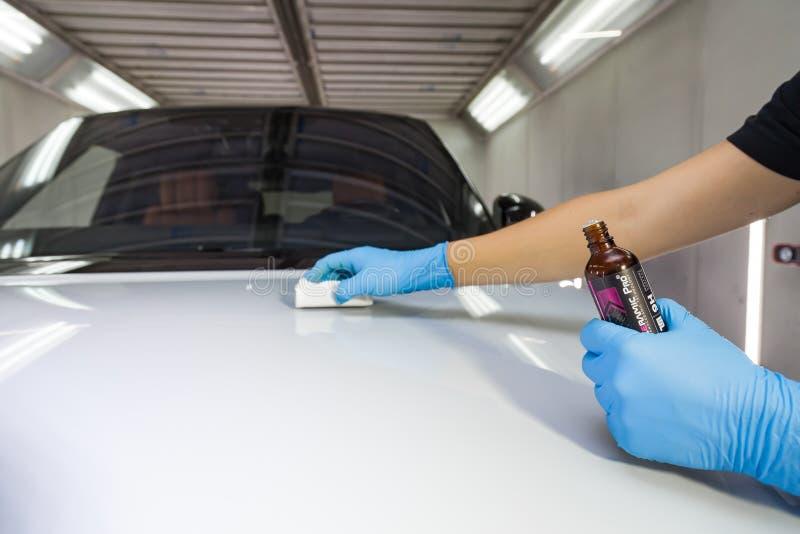 Le processus d'application d'un revêtement nano-céramique Ceramic Pro 9h et Light sur le capot de la voiture par un travailleur m photos libres de droits