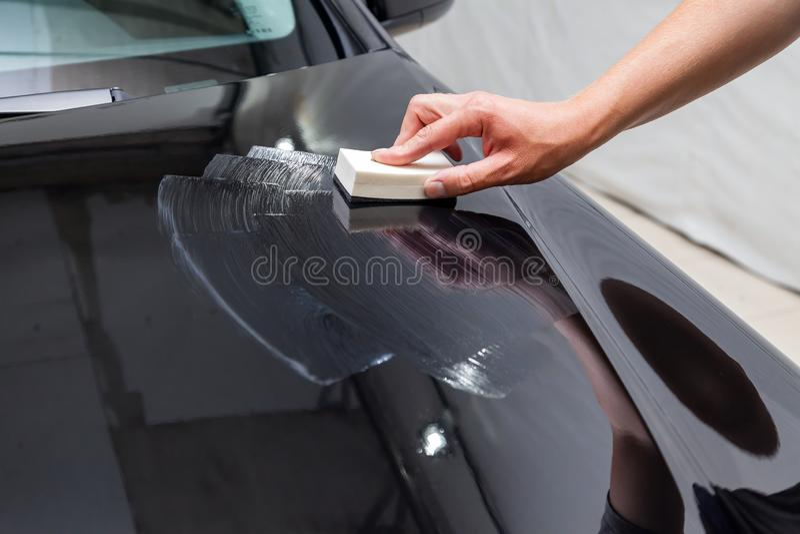 Le processus d'appliquer un revêtement nano-en céramique sur le capot de la voiture par un travailleur de sexe masculin avec une  photo libre de droits