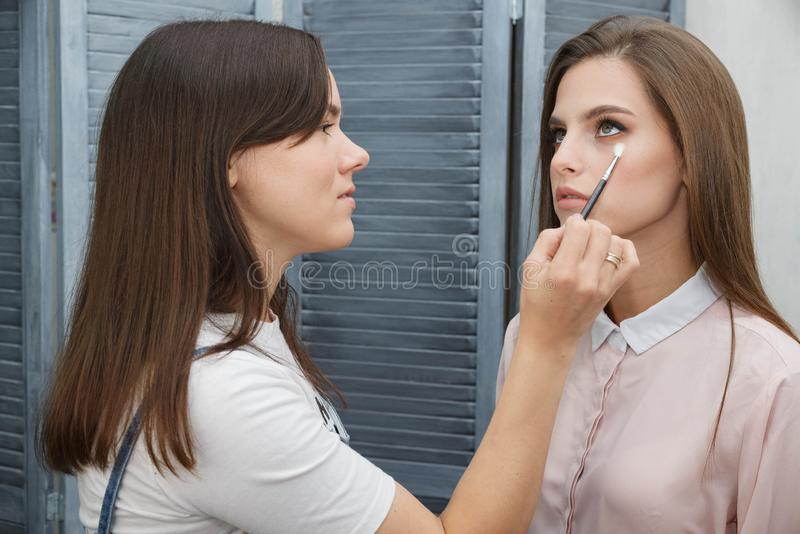 Le processus de cr?er le maquillage Maquilleur travaillant avec une brosse sur le visage du modèle photo libre de droits
