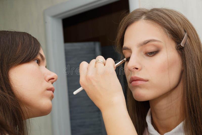 Le processus de cr?er le maquillage Maquilleur travaillant avec une brosse sur le visage du modèle image libre de droits