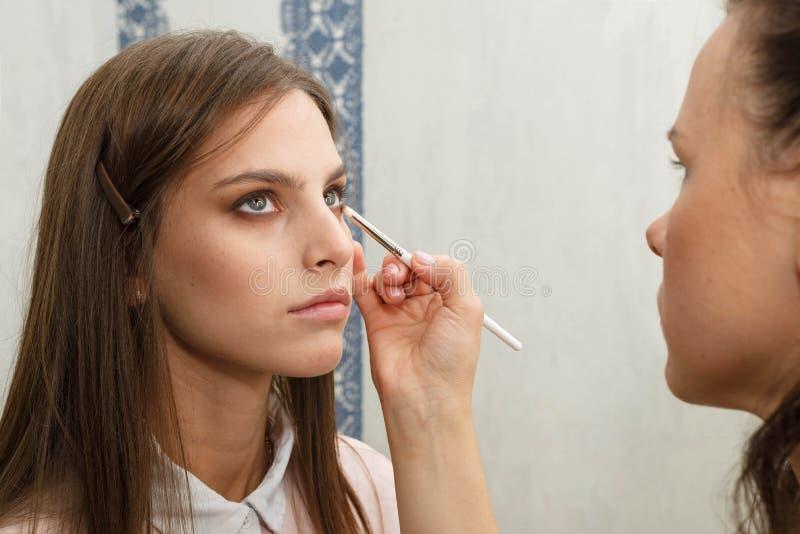 Le processus de cr?er le maquillage Maquilleur travaillant avec une brosse sur le visage du modèle photos libres de droits