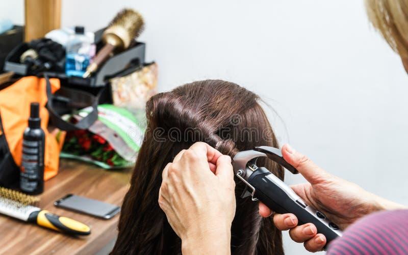 Le processus de grésillent tandis que coiffure images stock