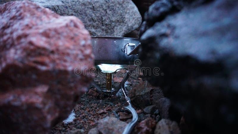 Le processus de la cuisson sur le brûleur Fourneau portatif parmi les pierres Le feu br?le photographie stock