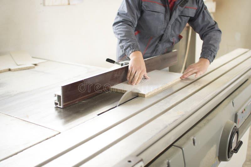 Le processus de plan rapproché du travailleur de charpentier avec la circulaire a vu la machine à la coupe de croix de faisceau e image stock