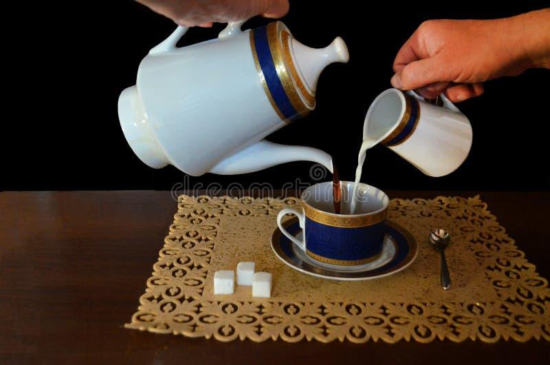 Le processus de verser le café avec du lait image stock